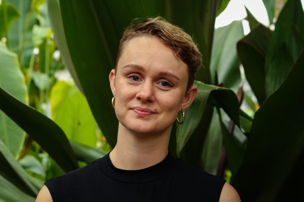a white non-binary person looks at the camera. their hair is light brown, they are smiling a little. they are wearing gold hoop earrings and a black top, and are standing against a background of green leaves.